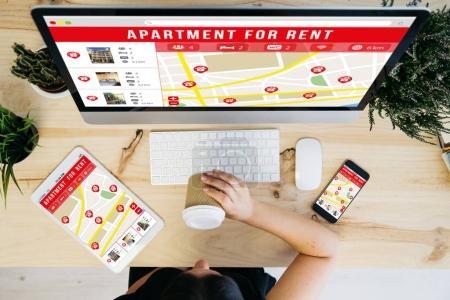 Photo pour Vue aérienne de femme buvant café et périphériques, montrant le site immobilier - image libre de droit