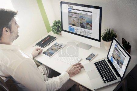 Photo pour Homme surfer sur Internet en utilisant ordinateur de bureau, ordinateur portable, tablette PC et smartphone - image libre de droit