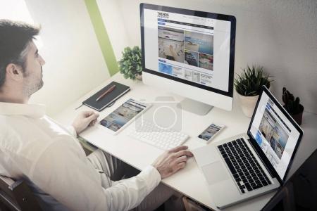 man surfing internet using desktop computer, laptop, tablet pc and smartphone
