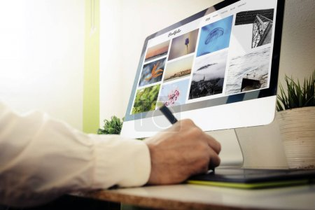 graphic designer checking online portfolio website using graphic tablet and desktop computer
