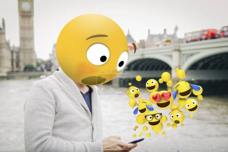 Man with emoji head surprised looking at smartphone in London city