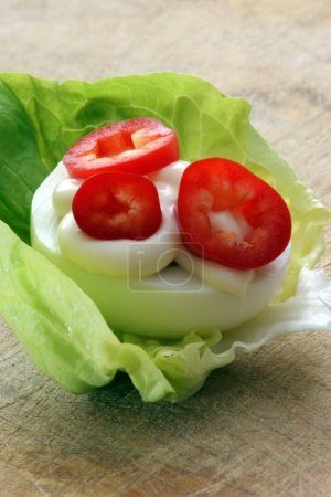 egg half with pepper pieces and mayonnaise on cabbage leaf, close-up
