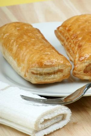 puff pastry with sausage filling on white plate, close-up