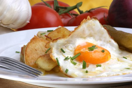 potato slices served with fried egg on white plate, close-up
