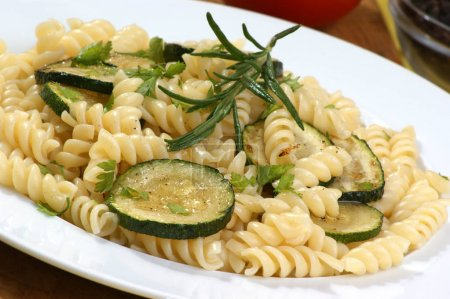 pasta with fried zucchini and rosemary on white plate, close-up