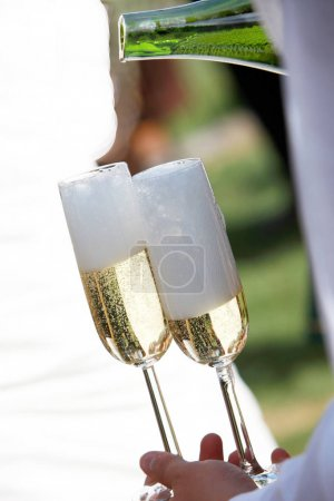 Two Champagne Glasses Are Filled with Waiter