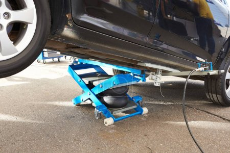 Car lifted by pneumatic jack