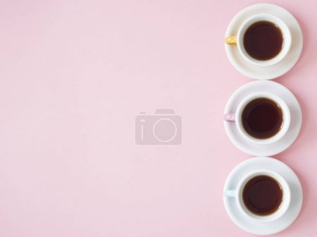 Top view of coffee cups on pink background