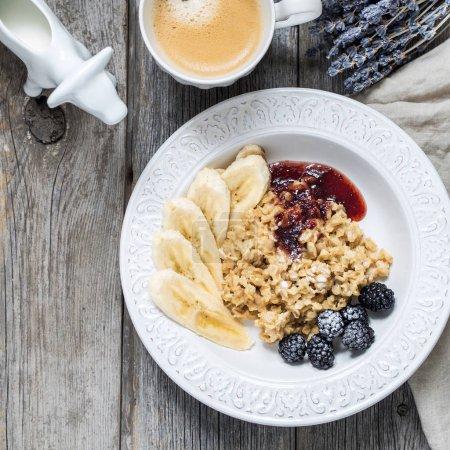 oatmeal served with raspberry jam, fresh berries, bananas and coffee