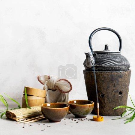 Photo pour Nature morte avec un ensemble à thé, furoshiki enveloppant présent cadeau, thé éparpillé, natte de bambou, baguettes, encens. Origine asiatique avec espace pour le texte. - image libre de droit