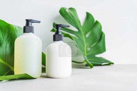 Photo pour Ensemble cosmétique de deux flacons vierges pour l'emballage maquette de crème de soin, shampooing, revitalisant sur fond gris avec des feuilles vertes. Concept de produits de beauté naturels . - image libre de droit