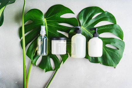 Photo for Cosmetic set of blank label bottles for mockup packaging of skincare product cream, serum, oil, shampoo, conditioner, perfume on grey background with green leaves. Natural beauty product concept. - Royalty Free Image