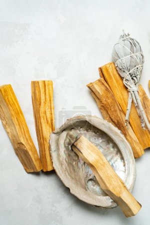 Photo for Smudge kit for spiritual practices with natural elements: Palo Santo sticks, dried white sage, Guinea Fowl feather, crystals, sea pearl shell Abalone on a light background. Balancing the soul. - Royalty Free Image
