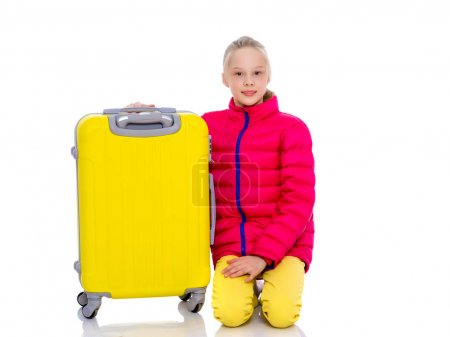 The girl gymnast with a large suitcase goes to the competition.