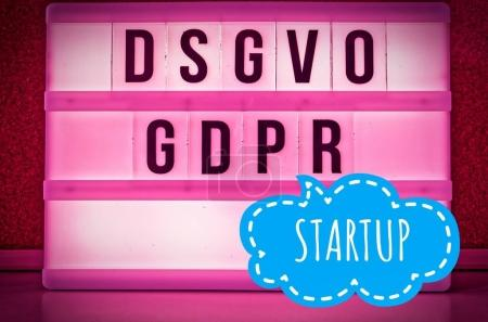 Illuminated board with the inscription DSGVO and GDPR (General Data Protection Regulation) yellow in English GDPR (General Data Protection Regulation) and the inscription Startup (New Company) in English: Startup