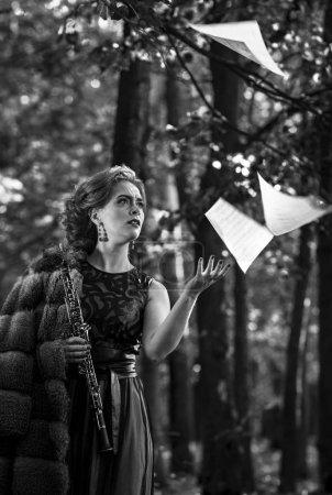 Photo pour Jeune femme séduisante tenant ébène jetant sur les feuilles de musique. Photo noir et blanc . - image libre de droit
