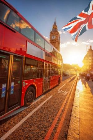 Big Ben with double decker bus against colorful sunset in London