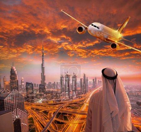 Photo pour Homme arabe avec avion survolant de Dubaï contre le coucher de soleil coloré dans les Émirats Arabes Unis - image libre de droit