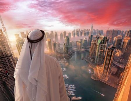 Photo pour Arabian man regarde la marina de Dubaï à Dubaï, Émirats arabes unis . - image libre de droit