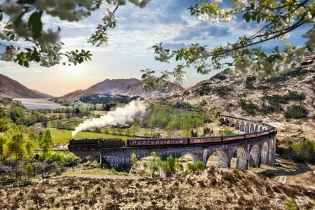 Photo for Glenfinnan Railway Viaduct in Scotland with the Jacobite steam train against sunset over lake - Royalty Free Image