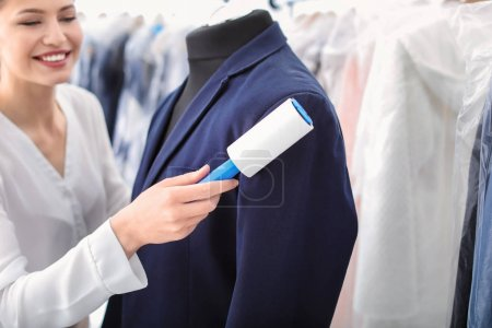 Young woman removing dust from jacket with lint roller at dry-cleaner's