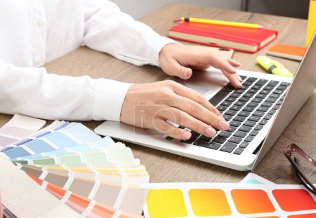 Woman working with laptop and palette samples at w...
