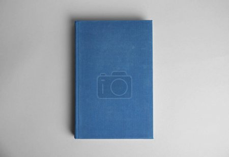 Hardcover book on light grey background, top view....