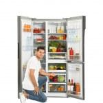 Man near open refrigerator on white background...