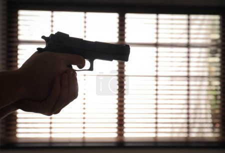 Photo for Man holding gun indoors, closeup. Space for text - Royalty Free Image