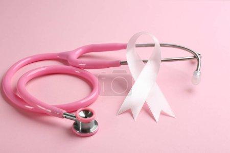Photo pour Ruban rose et stéthoscope sur fond coloré, fermeture. Concept de cancer du sein - image libre de droit