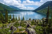 Lake in the mountains surrounded by old trees and large boulders. Wild remote place in the mountains. Huge boulders and old trees allow to forget about civilization.