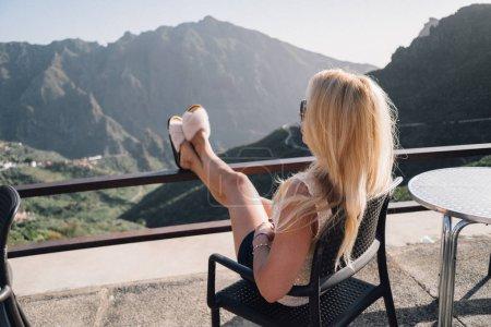 Photo pour Jeune femme assise sur une chaise noire sur la terrasse d'observation et regardant les montagnes - image libre de droit