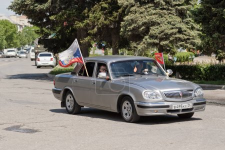 Cars decorated with flags driving around city streets in celebra