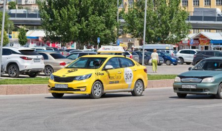 "New yellow car of service ""Yandex taxi"" on city road"