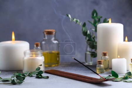 Photo pour Incense stick with smoke on stone with white candles and essential eucalyptus oil - image libre de droit