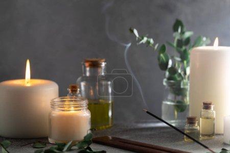 Photo pour Bâton incandescent avec de la fumée sur pierre avec des bougies blanches et de l'huile essentielle d'eucalyptus - image libre de droit