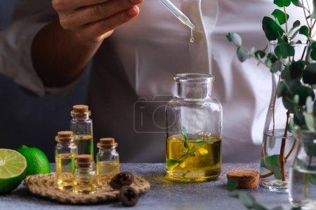 Photo pour Woman hand pouring eucalyptus essential oil into bottle on grey table lime - image libre de droit