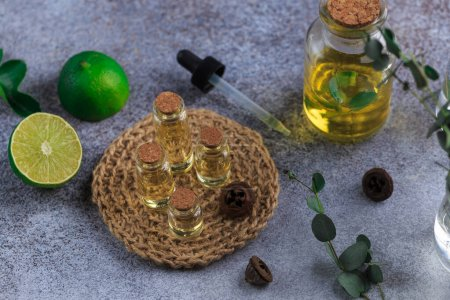 Photo pour Set of glass bottles with eucalyptus essential oil on grey table leaves in vase lime - image libre de droit