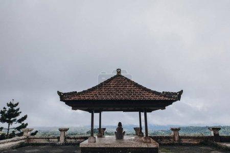 Photo for Back view of girl sitting on terrace at hotel pondok indah bedugul, bali - Royalty Free Image