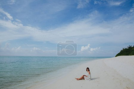Photo for Beautiful young woman in sunglasses and dress resting on sandy beach at Ukulhas island, Maldives - Royalty Free Image