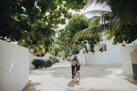 Photo for UKULHAS, MALDIVES - 27 JANUARY, 2018: man riding bicycle on street at  Ukulhas island, Maldives - Royalty Free Image