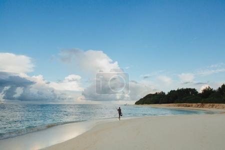 Foto de Pescador irreconocible caminando por playa de arena Thoddoo isla, Maldivas - Imagen libre de derechos