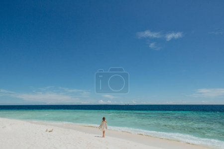 Photo for Back view of girl walking on sandy beach at Thoddoo island, Maldives - Royalty Free Image