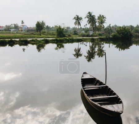 Photo pour Vider le bateau en bois sur l'eau à Hoi An, Vietnam - image libre de droit