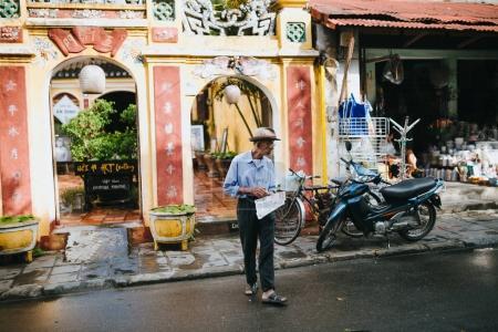 Photo pour Hoi An, Vietnam - 3 janvier 2018: senior homme vietnamien avec journal de marche dans la rue à Hoi An, Vietnam - image libre de droit
