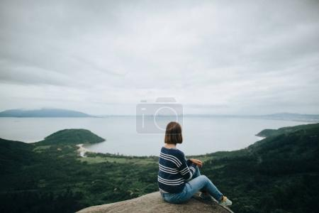 Photo for Back view of young woman sitting on cliff and enjoying amazing landscape in Hai Van Pass, Vietnam - Royalty Free Image
