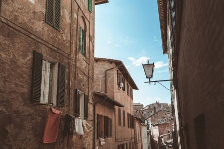 Photo for Narrow street with arch in historical quarter of Siena - Royalty Free Image