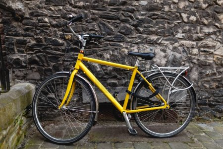 Photo for Modern yellow bicycle near old stone wall in Ghent, Belgium - Royalty Free Image