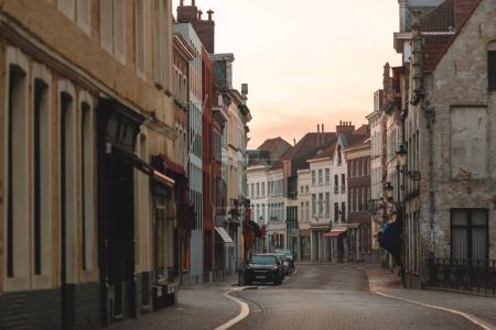 Photo for BRUGGE, BELGIUM - NOVEMBER 02, 2016: narrow street with beautiful old houses and cars at sunset, brugge, belgium - Royalty Free Image