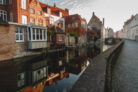 Photo for BRUGGE, BELGIUM - NOVEMBER 02, 2016: pavement on narrow street and buildings reflected in calm water of canal in brugge, belgium - Royalty Free Image